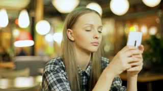 Young girl texting on smartphone while sitting in the cafe