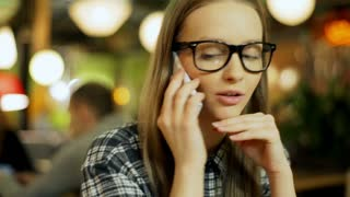 Young girl wearing glasses and talking on cellphone in the cafe