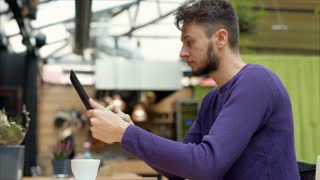 Young man browsing internet on tablet and smiling to the camera, steadycam shot