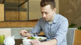 Young man eating lunch in the cafe and having a toothache