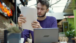 Young man reading papers and doing serious look to the camera, steadycam shot