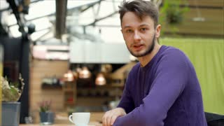 Young man sitting in the cafe and chatting with someone, steadycam shot