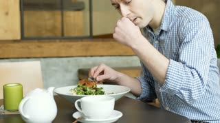 Young man sitting in the cafe and eating fit, healthy lunch, steadycam shot