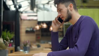 Young man sitting in the cafe and receiving bad news while speaking on cellphone