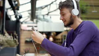 Young man wearing headphones and having a videocall on smartphone, steadycam sho