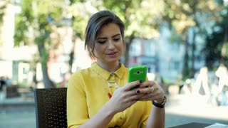 Young, stylish woman sitting in the outdoor cafe and browsing internet on smartp
