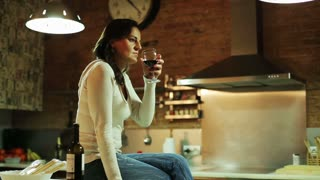Young woman drinking red wine in her kitchen
