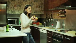 Young woman eating orange in her kitchen