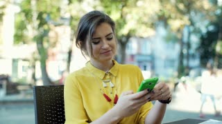 Young woman in yellow shirt sitting in the outdoor cafe and talking on cellphone