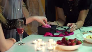 young woman opening gift at bachelorette party, slow motion shot at 240fps