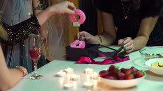 young woman opening gift at bachelorette party, slow motion shot at 60fps