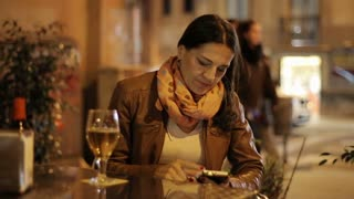 Young woman waiting for somebody in the restaurant at night, steadycam shot