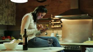 Young woman with cellphone drinking red wine in her kitchen