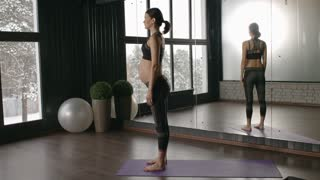 30weeks pregnant woman doing downward dog calf stretch on mat while practicing yoga in studio