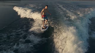 Above view of athletic man riding surf