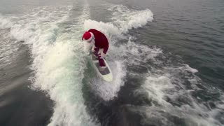 Above view of man is Santa Claus disguise wakesurfing professionally gesticulating thumbs up