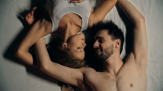 Above view of sweet lovers lying jack in bed and kissing
