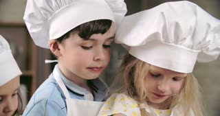 Adorable children tasting sweets in cooking class