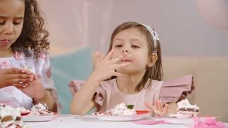 Adorable little princesses eating birthday cake at the table and licking fingers in slow motion