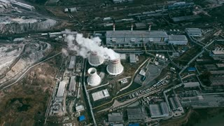 Aerial shot of power plant with cooling towers rejecting waste heat to atmosphere and producing steam surrounded by factories in large industrial area