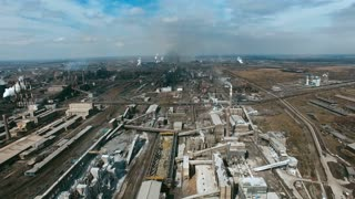 Aerial view of large industrial area and metallurgical plant with smoke stacks polluting air