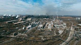 Aerial view of metallurgical plant with chimneys smoking and polluting air and power station with cooling towers producing steam in large industrial area