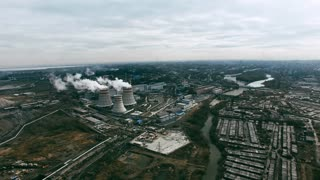 Aerial view of power plant and cooling towers producing steam surrounded by large industrial area
