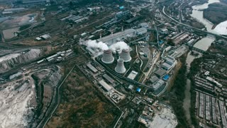 Aerial view of power station with cooling towers producing steam surrounded by industrial area with factories and countryside