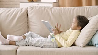 African girl lying on comfortable sofa at home and swiping the screen of digital tablet
