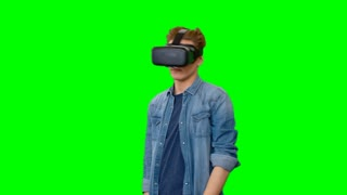Amazed young man in virtual reality glasses standing against green background looking around and on his hands with open mouth