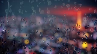 Animated background with drops of pure water flowing down window glass with defocused street lights behind it