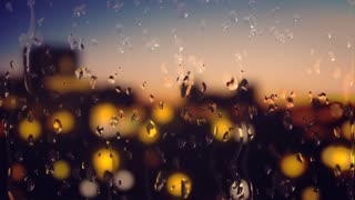 Animated background with water droplets falling down on window glass with defocused street lights behind it