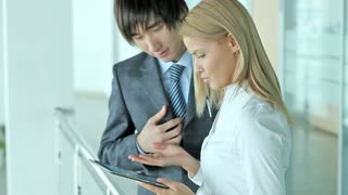 Asian businessman presenting business options on the screen of a tablet computer to his female colleague