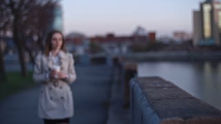 Beautiful woman walking alone on the riverside, drinking coffee from paper cup and enjoying picturesque view of city in the evening