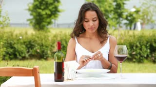 Beautiful young woman enjoying her meal and local red wine in the open air