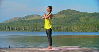 Beautiful young woman having outdoor yoga practice near lake