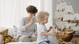 Blond curly toddler with plump cheeks playing with toys and ship model while his mother in glasses taking pictures of him on tablet