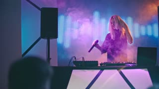 Blond female DJ dancing behind decks, then picking up microphone and singing into it for cheering crowd