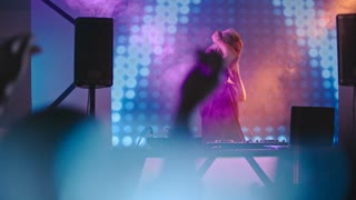 Blond female DJ dancing behind mixer console surrounded by smoke and colorful LED projection