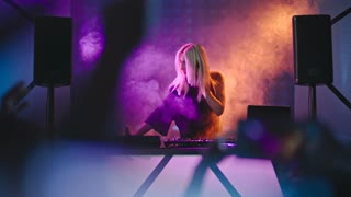 Blond female DJ with headphones dancing and singing behind mixer console at concert in nightclub