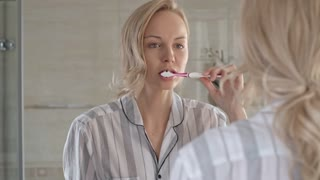 Blonde woman brushing teeth in front of the mirror in bathroom