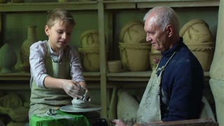 Boy failing to make a clay vase on a pottery wheel