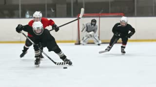 Boy in black uniform skating towards the camera and handling the puck whiles his opponent and teammate trying to reach him. Filmed with Sony Nex 700