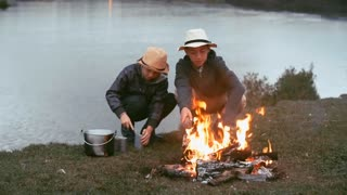 Boy making a fire on the riverbank whiles his friend opening can with food like Tom Sawyer and Huckleberry Finn during the escape from home