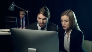 Business discussion in dark office, two people businessman and businesswoman in suits sitting at desk, looking at computer screen, talking and gesturing while third man out of focus in the background typing