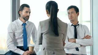 Business team of three having a briefing at the office window, woman standing with her back to the camera