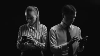 Businessman and businesswoman standing in dark studio and typing something on their smartphones and looking at camera in the end of the video