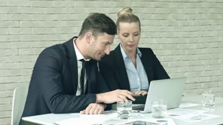 Businessman explaining to female colleague how to do business report