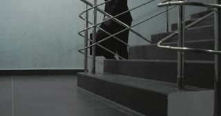 Businessman with briefcase in his hand walking upstairs in business center