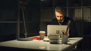 Businessman working alone in his office in the evening